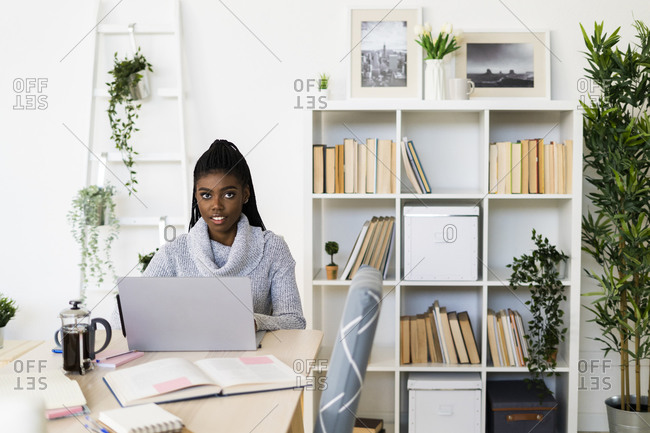 Female student E-learning on laptop while sitting at home