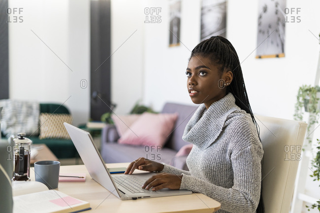Young woman looking away while studying on laptop sitting at home