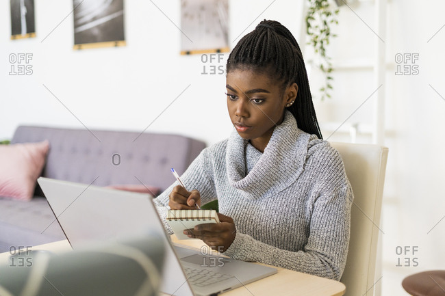 Female student writing in notepad while studying through laptop at home