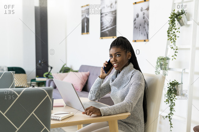 Smiling female student talking on smart phone while studying through laptop at home