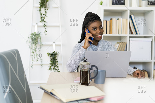 Smiling woman talking on smart phone while studying through laptop at home