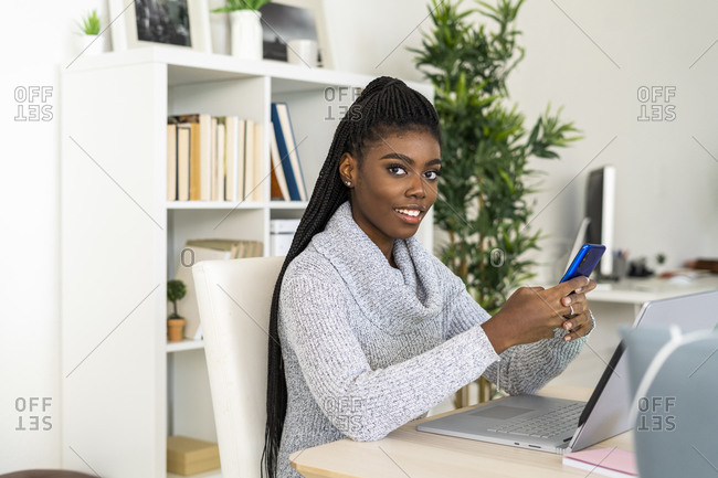 Female student using smart phone while E-learning on laptop while sitting at home