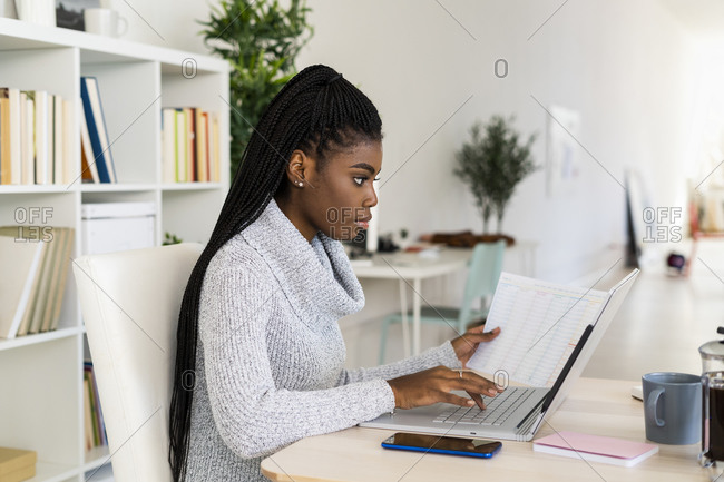 Female student concentrating while reading paper studying on laptop at home