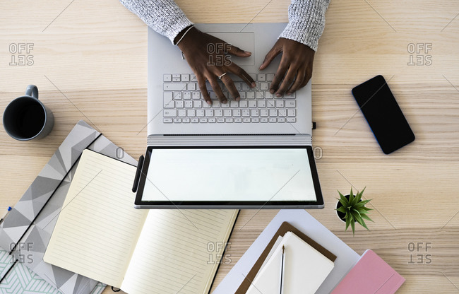 Hands of female entrepreneur using laptop while studying at home