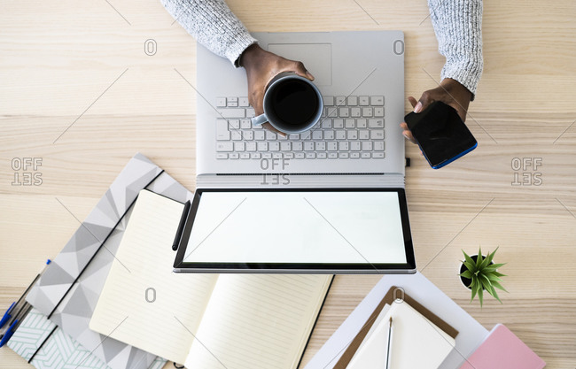 Hands of female freelancer holding coffee cup and smart phone while studying at home