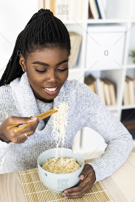 Woman eating noodles with chopsticks while sitting at home