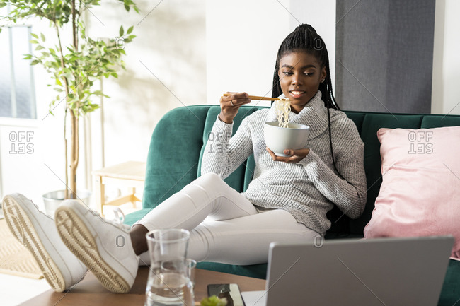 Young woman eating noodles while watching movie on laptop sitting in living room at home