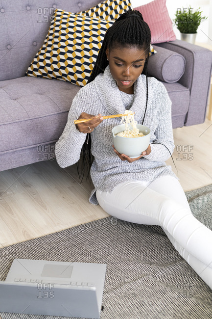 Young woman eating noodles while sitting on floor in living room at home