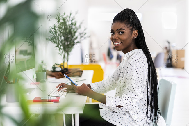 Smiling female entrepreneur using smart phone while working on computer in home office