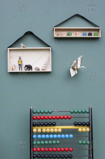Abacus and toys on DIY shelves hanging on leather strips