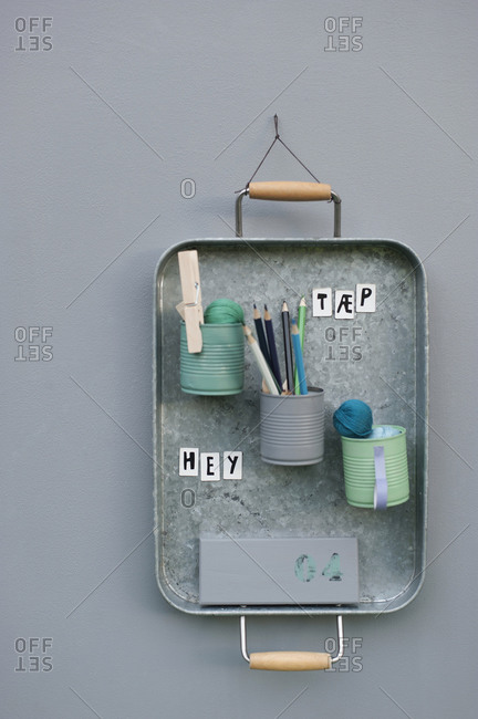 Office supplies in cans attached to metal tray hanging on wall