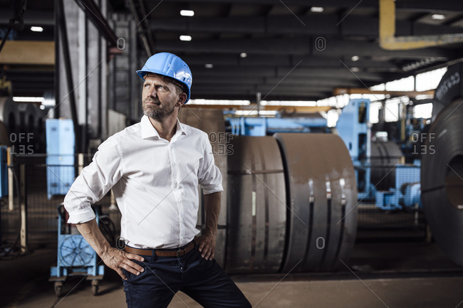 Male entrepreneur with hand on hip looking away while standing in industry