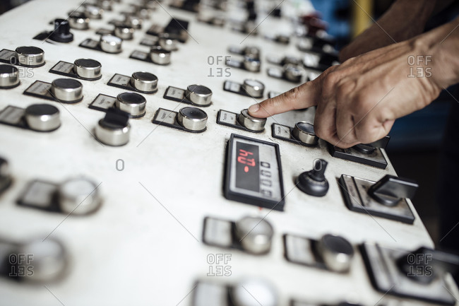 Man's hand operating control panel in factory