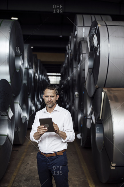 Male entrepreneur holding digital tablet while standing in manufacturing industry