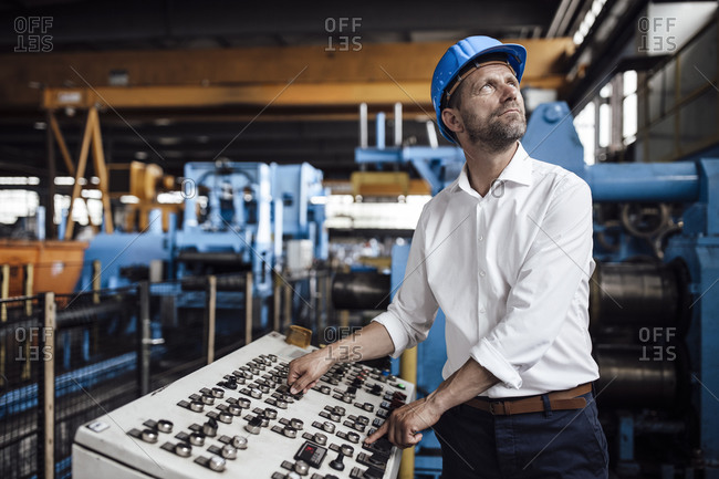 Male entrepreneur operating control panel looking up while standing at industry