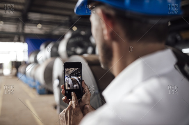 Businessman taking picture through smart phone in industry