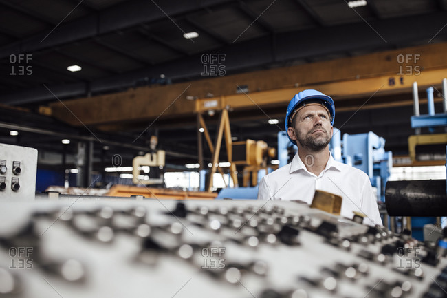 Thoughtful businessman looking up while standing in factory