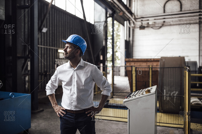 Smiling businessman with hands on hip looking up while standing in industry