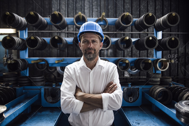 Male entrepreneur with arms crossed standing in steel mill