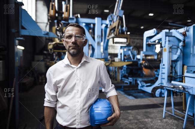 Male entrepreneur wearing protective eyewear while holding helmet standing in factory