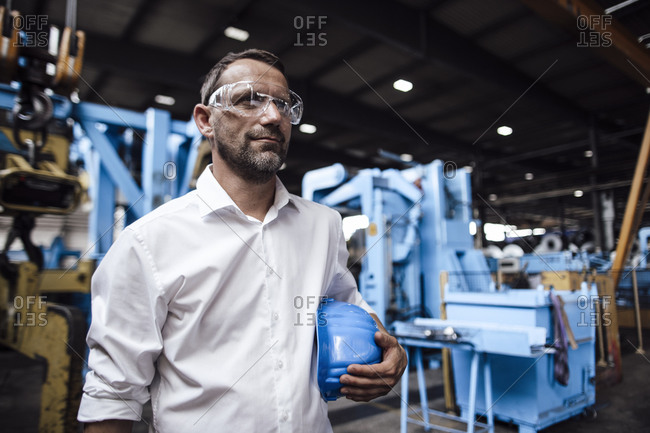 Businessman wearing protective eyewear while holding helmet standing at industry