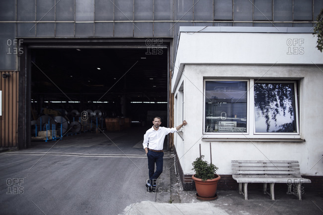 Businessman leaning on cabin while standing against factory entrance