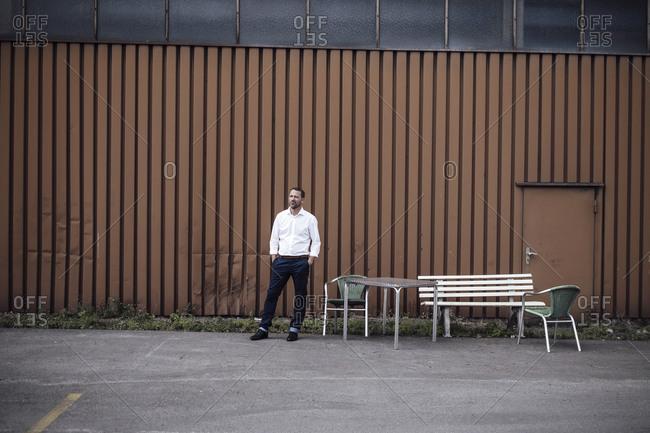 Businessman looking away while standing in parking lot against metal door
