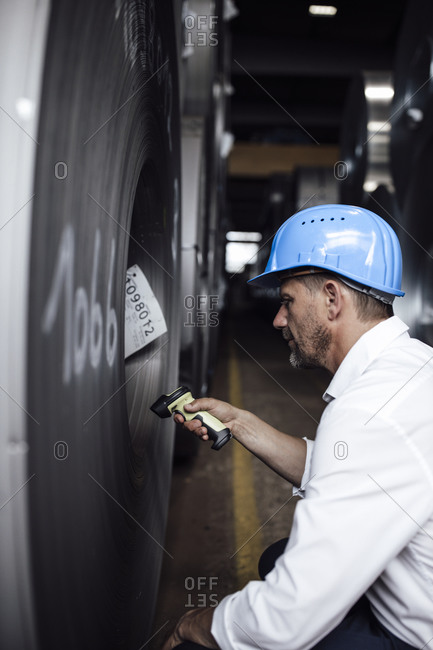 Businessman scanning barcode on steel rolls while standing in industry