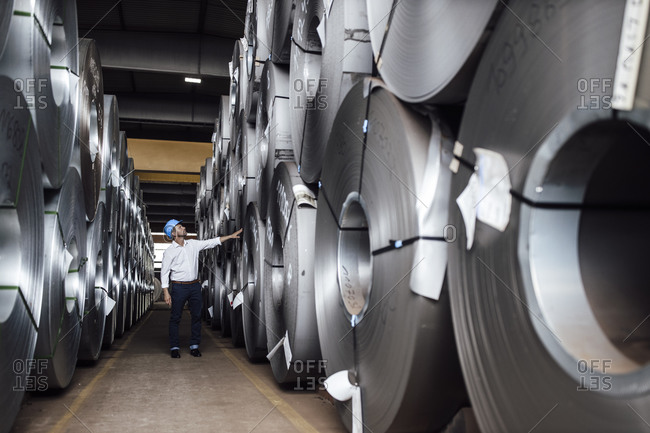 Businessman analyzing steel rolls while standing in industry