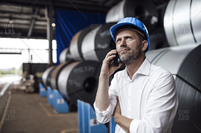 Male owner talking on smart phone looking up while standing against steel rolls in industry