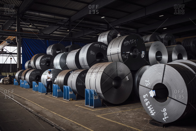 Businessman standing against steel rolls at factory