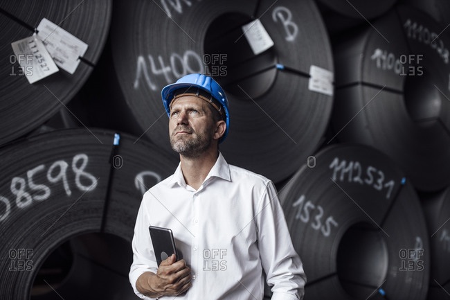 Male entrepreneur holding digital tablet looking up while standing against steel rolls in factory