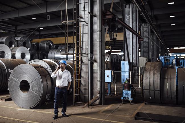 Male entrepreneur talking on smart phone looking up while standing against steel rolls in industry