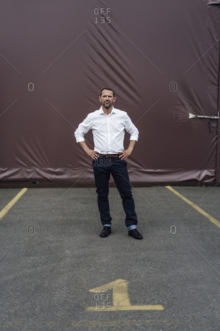 Businessman with hands on hip standing in parking lot