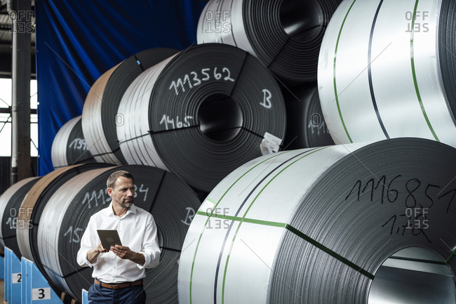 Businessman holding digital tablet examining steel rolls while standing in factory