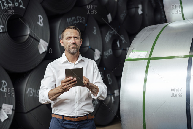Male entrepreneur holding digital table while standing against steel rolls in factory