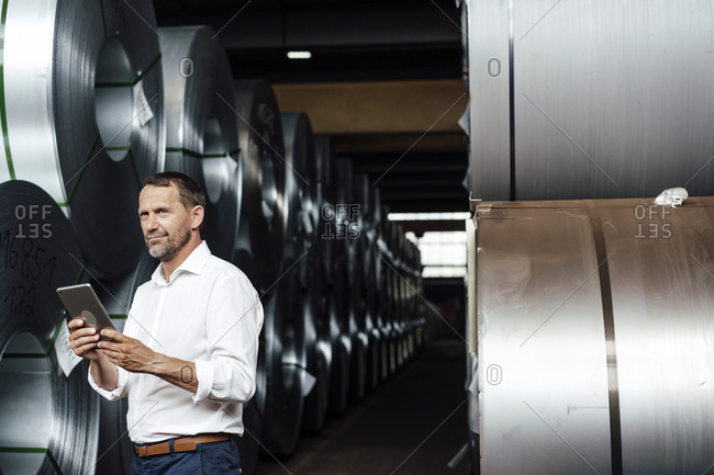 Businessman holding digital table while standing by steel rolls at industry