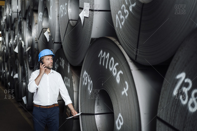 Businessman talking on smart phone while examining steel rolls at factory