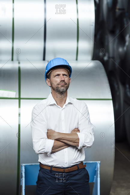 Thoughtful businessman with arms crossed standing against steel rolls in factory