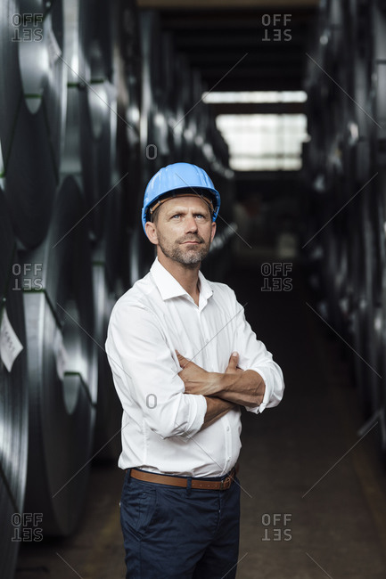 Businessman contemplating with arms crossed standing by steel rolls in factory