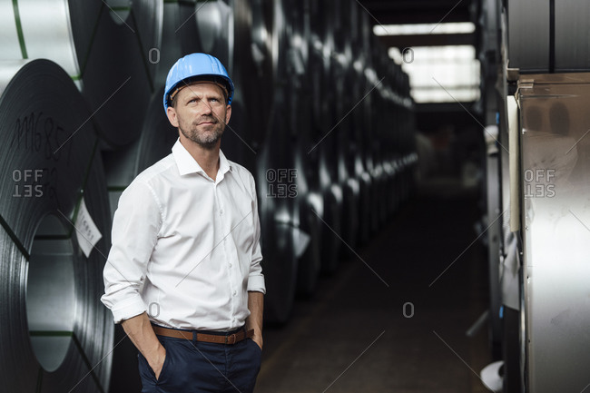 Businessman contemplating with hands in pockets standing by steel rolls in factory