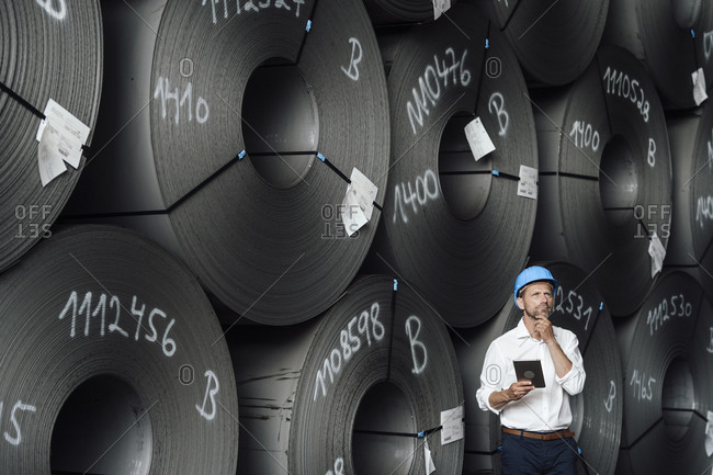 Male entrepreneur with hand on chin holding digital tablet while standing against steel rolls in factory