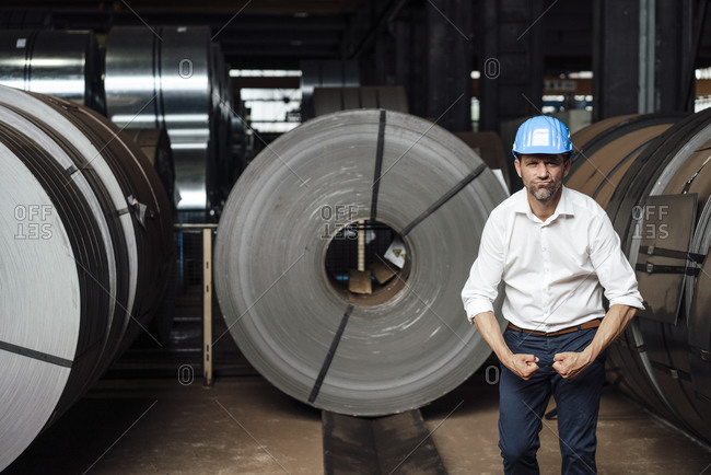 Businessman flexing muscles while standing in factory