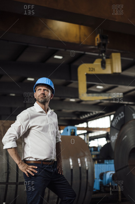 Confident businessman with hands on hip looking up while standing in factory