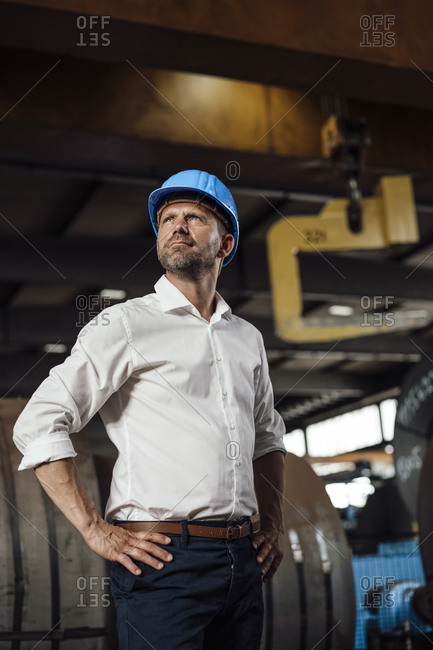 Businessman with hands on hip looking up while standing in factory