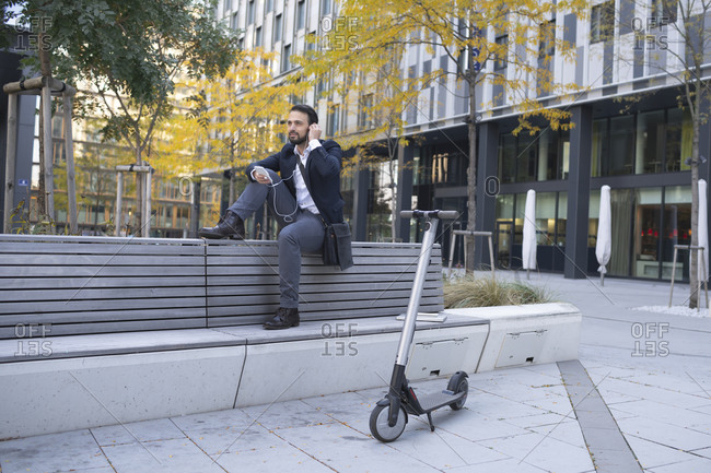 Businessman with in-ear headphones sitting on retaining wall in city