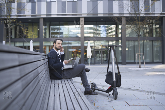 Businessman using in-ear headphones while sitting on retaining wall in city