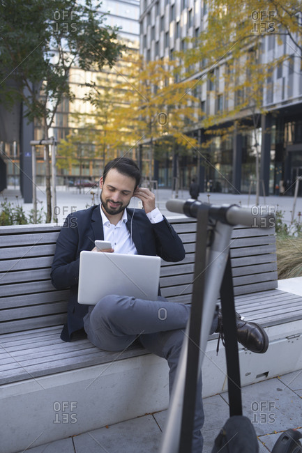 Businessman using in-ear headphones on retaining wall in city