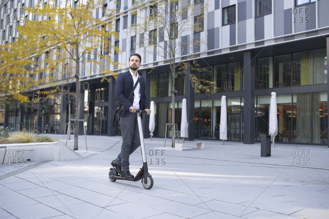 Businessman riding on electric scooter against building in city