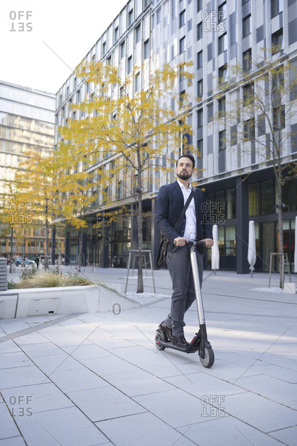 Male business person riding on electric scooter against building in city